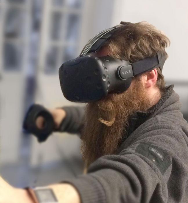 Foto: junger Mann mit langem Vollbart und VR-Headset
