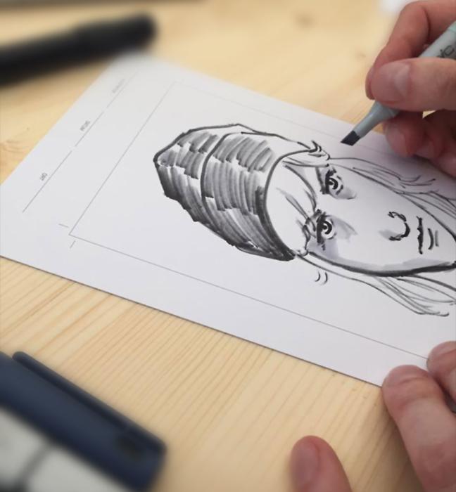 Foto: Nahaufnahme einer Hand, die gerade das Portrait einer jungen Frau zeichnet