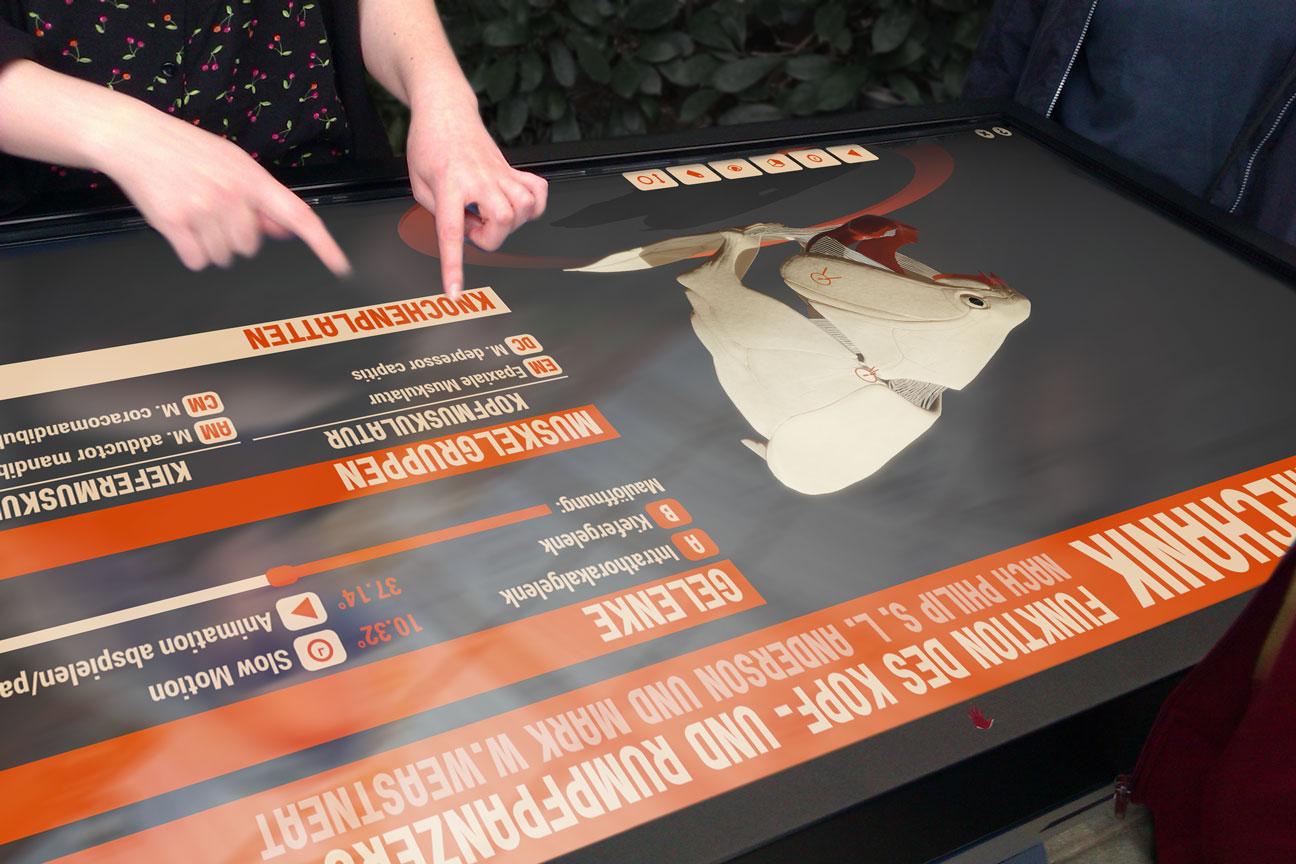 Fotomontage: Frauenhände bedienen die Panzerfisch-App auf einem riesigen tischförmigen Touchscreen.